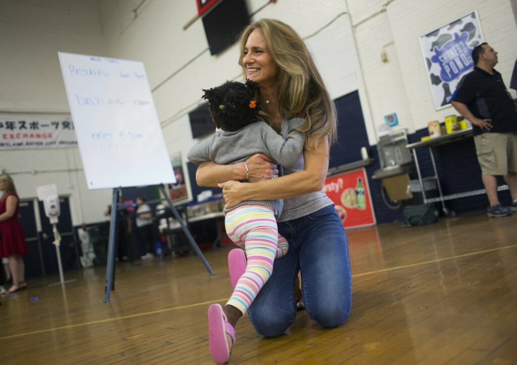 Volunteer Julie Haddad of Scarborough gives a hug to Melissa Paoula Ononye, 10, at the emergency shelter for asylum seekers at the Portland Expo.