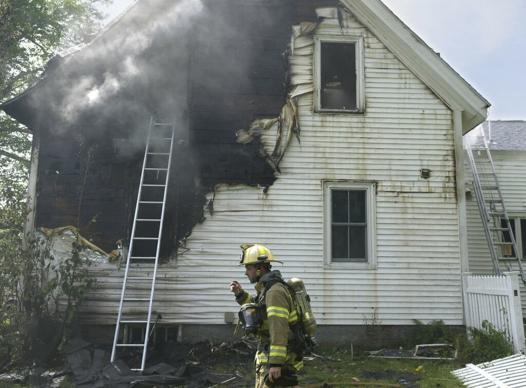 A firefighters surveys a house that was damaged by fire Tuesday on Prescott Road in Manchester.