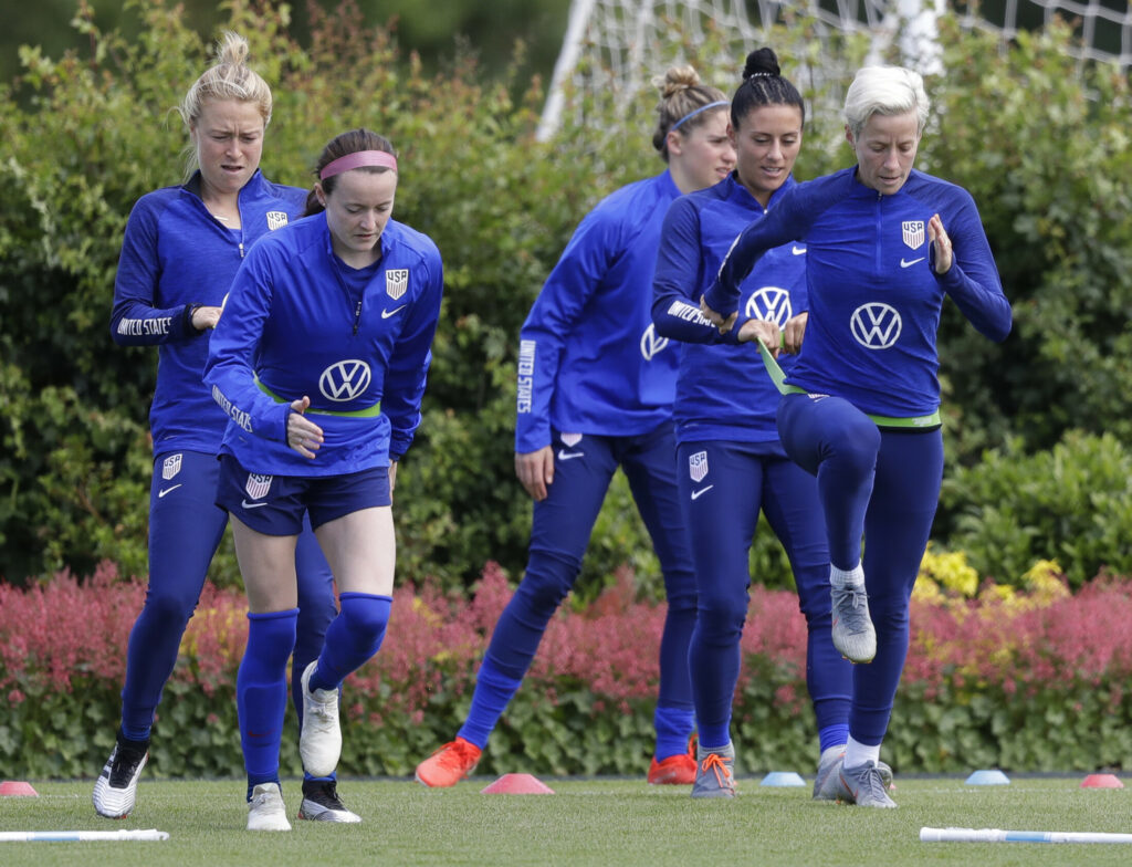US player Megan Rapinoe, front right, stretches with Ali Krieger and other team members during a US womens soccer team training session at the Tottenham Hotspur training centre in London, Thursday, June 6, 2019. The Women's World Cup starts in France on June 7. (AP Photo/Kirsty Wigglesworth)
