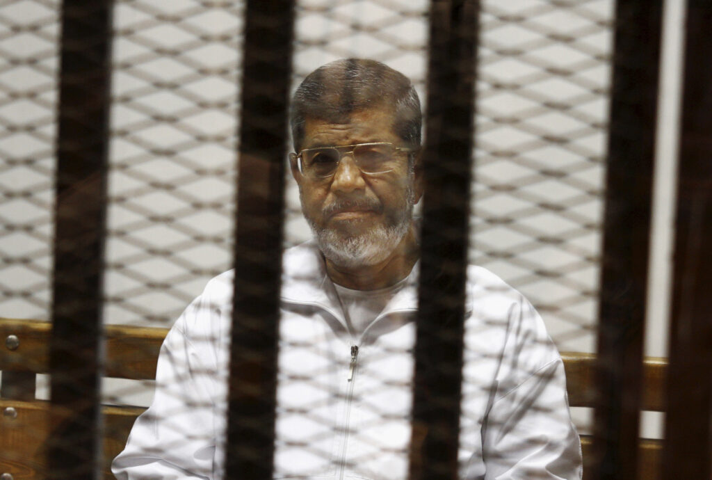 Egypt's ousted Islamist President Mohammed Morsi sits in a defendant cage in the Police Academy courthouse in Cairo in 2014. On Monday, Egypt's state TV said Morsi, 67, collapsed and died while he was attending a court trial on espionage charges.