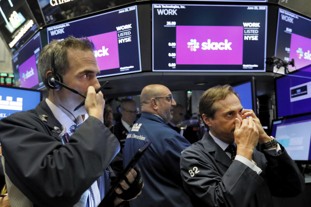 Traders Gregory Rowe, left, and Dudley Devine, right, talk into their mobile phones on the floor of the New York Stock Exchange on Thursday.