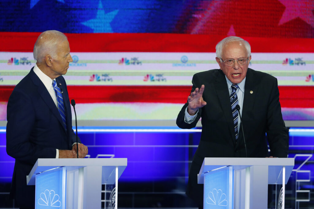 Sen. Bernie Sanders, I-Vt., speaks during Thursday night's Democratic debate as former Vice President Joe Biden watches. The debate underscored the deep ideological divisions among the Democratic candidates for president.