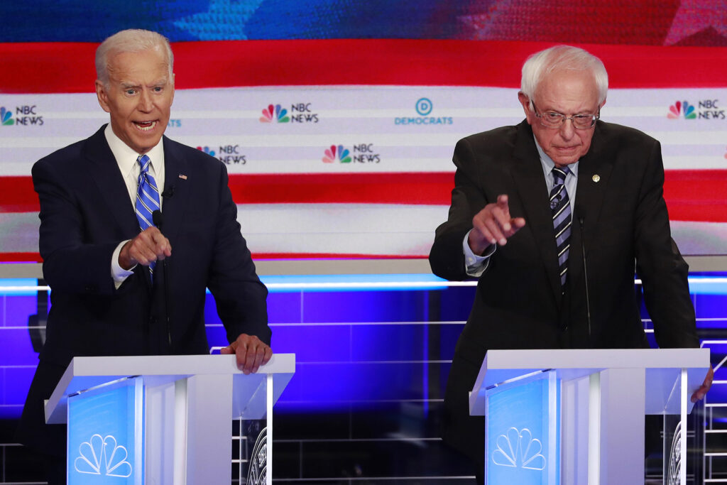 Former Vice President Joe Biden, left, and Sen. Bernie Sanders, I-Vt., speak at the same time during Thursday night's Democratic debate  in Miami. The raucous debate highlighted the deep ideological divisions among the Democratic candidates.
