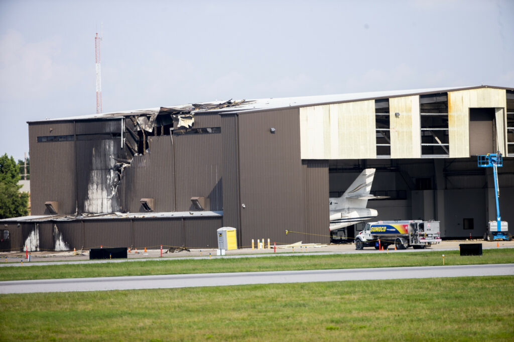 A hangar shows damage after a twin-engine plane crashed into it at Addison Airport in Addison, Texas, on Sunday.