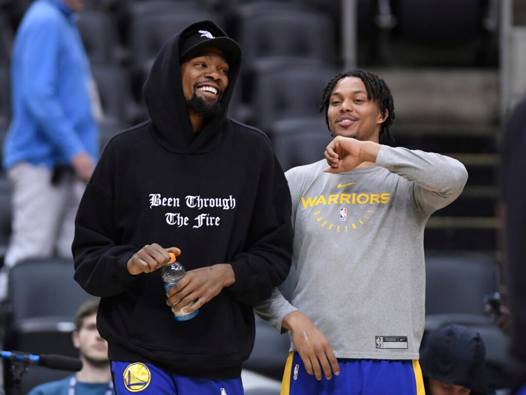 Golden State Warriors Kevin Durant, left, laughs with teammate Damion Lee during practice Saturday in Toronto, Saturday. The Warriors hope Durant will be available for Game 5 on Monday.