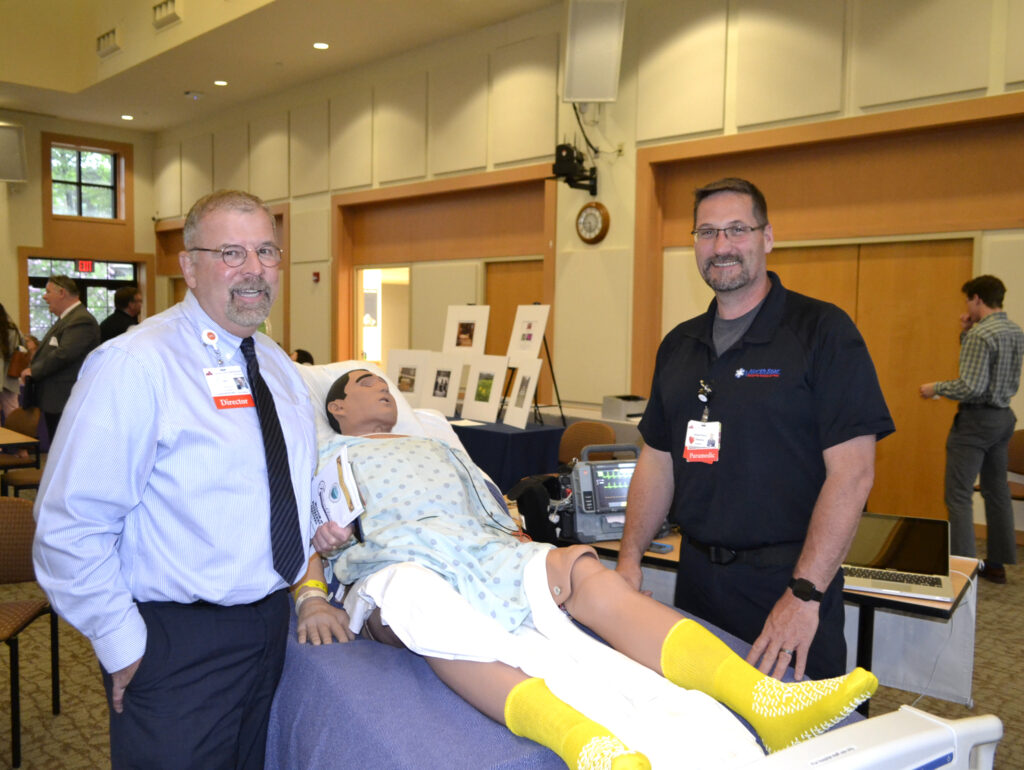 Franklin Memorial Hospital employees Bertrand Dugal and Michael Senecal flank a patient simulator used for a demonstration.