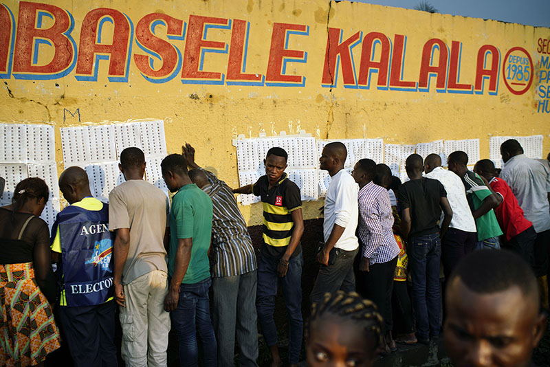 Election officials tape voter registration lists to a wall of the Les Anges primary school in Kinshasa, Congo, as voters start to check their names, Sunday Dec. 30, 2018. The election process was delayed when voters burned six voting machines and ballots midday, angered by the fact that the registrations lists had not arrived. Replacement machines had to be brought in, and voting started at nightfall, 12 hours late. Forty million voters are registered for a presidential race plagued by years of delay and persistent rumors of lack of preparation. Associated Press/Jerome Delay
