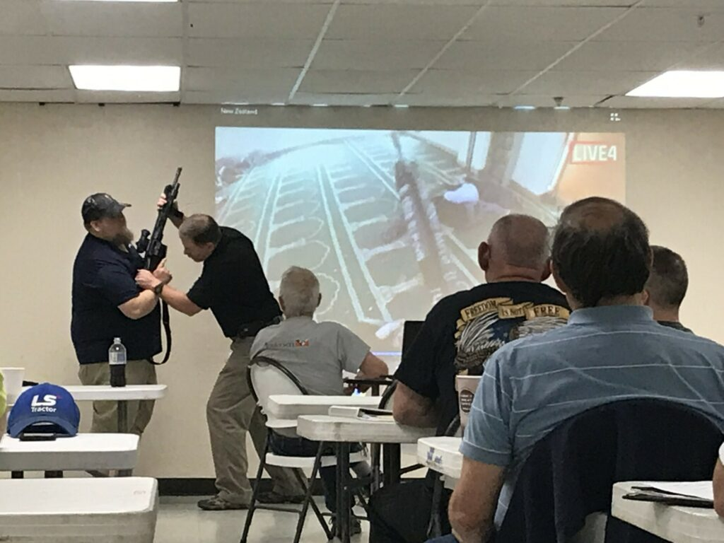 Peter Joyce, of Special Reaction Team Concepts, demonstrates on Saturday how to disarm an intruder. He was addressing representatives of several central Maine religious groups in Winslow.
