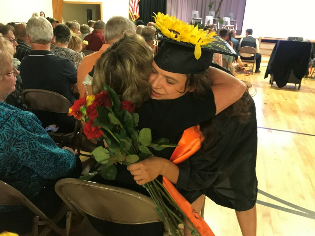 Hannah Harmon, a 2019 graduate of Forest Hills Consolidated School, gives a flower to her former art teacher in another district and friend Susan Beaulier during commencement Saturday.