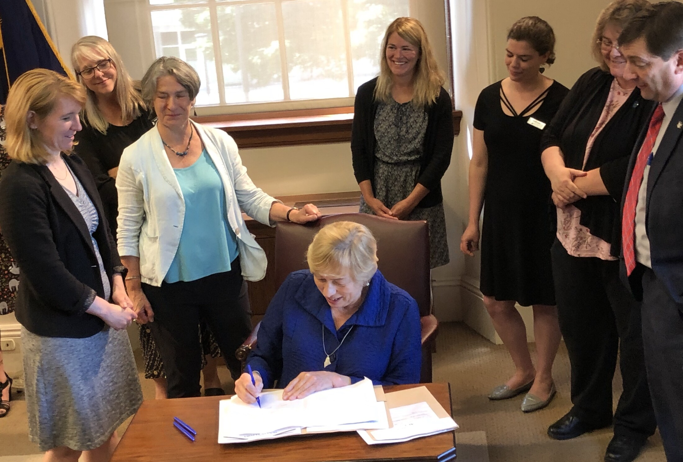 Gov. Janet Mills signs bills aimed at lowering drug prices and increasing industry transparency as state lawmakers and advocates for prescription drug price reform gather in the Cabinet room at the State House on Monday.