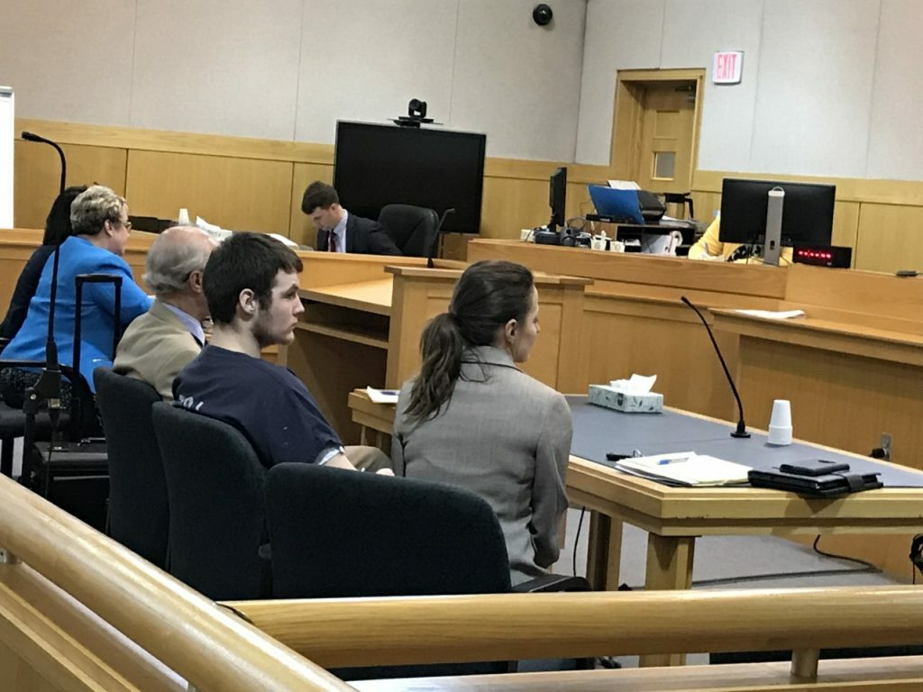 Dominic Sylvester, center, appears in West Bath District Court between his attorneys in June 2019. He is charged with depraved indifference murder in the death of his grandmother in February 2018.