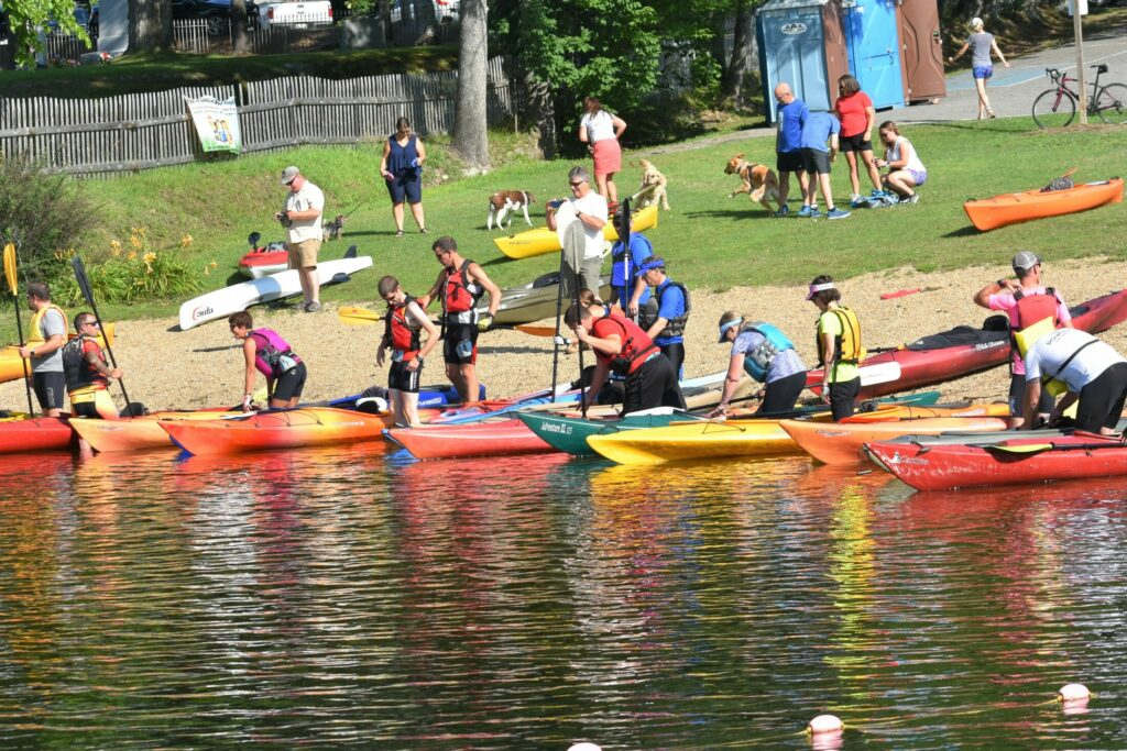 """Kayakers on Messalonskee Lake prepare for the first leg of the Paddle, Pedal and Pound Triathalon at last year's Oakfest. The event includes a 2.5 mile kayak/canoe, a 12-mile bike ride and a 3.1 mile run to the finish. To register, visit """"Events"""" at oakfestmaine.com."""