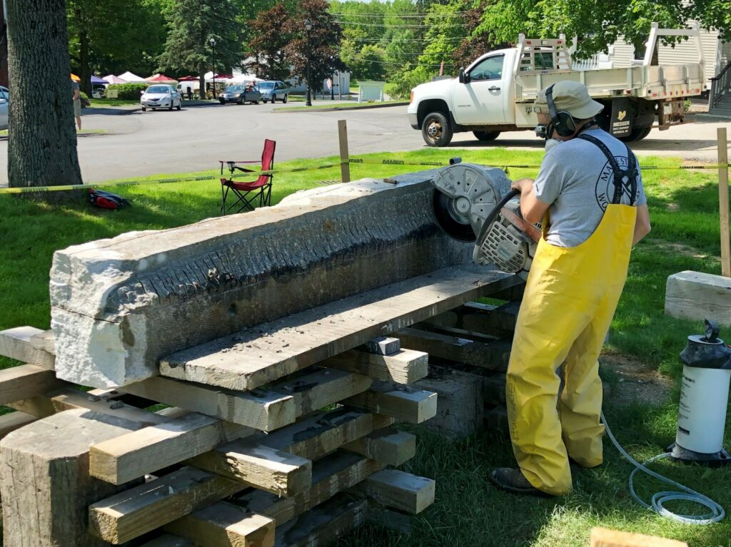 Sculptor Jon Doody uses a demolition saw to remove material from a block of granite Saturday that he plans to turn into a sturgeon at Stevens Commons in Hallowell.