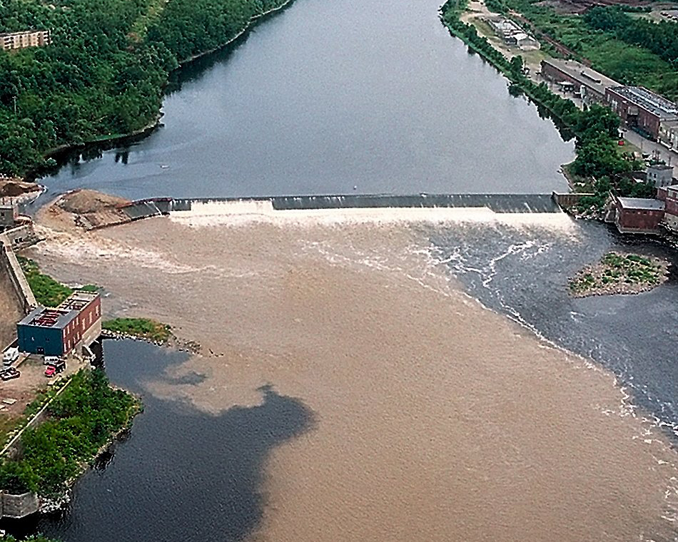 The Kennebec River is clouded with dirt and silt as the rushing waters from the upper section of the river flow freely through the breach (at left) in Edwards Dam in July 1999.