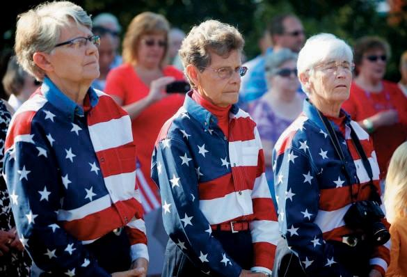 The Freeport Flag Ladies, from left, Elaine Greene, Carmen Footer and JoAnn Miller, listen at a 2013 ceremony marking the anniversary of Sept. 11, 2001.