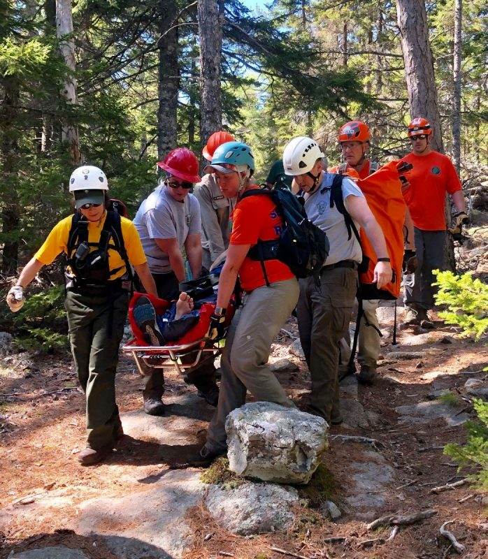 Rescuers carry out one of the two hikers who fell in Acadia.