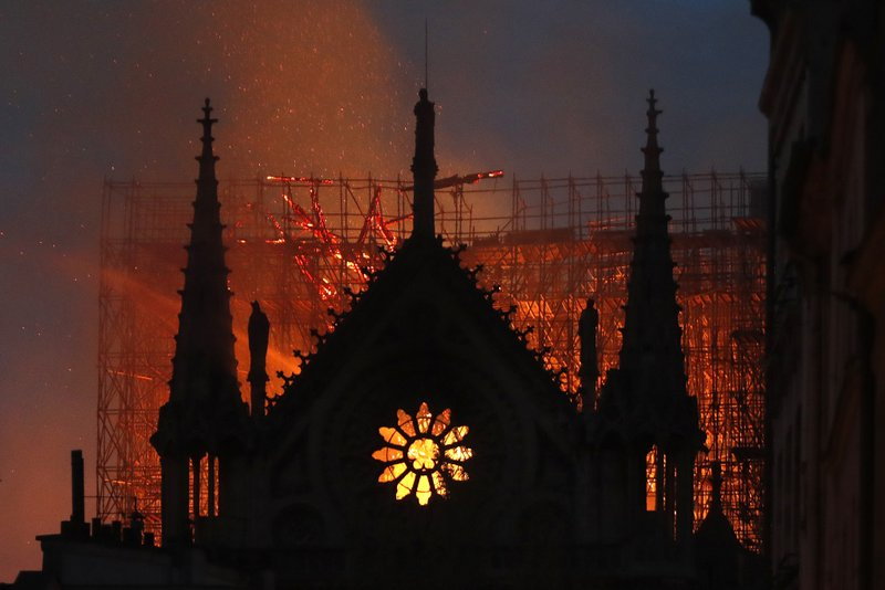 Flames and smoke rise from Notre Dame cathedral as it burns in Paris, Monday, April 15, 2019. Massive plumes of yellow brown smoke filled the air above Notre Dame Cathedral and ash fell on tourists and others around the island that marks the center of Paris.