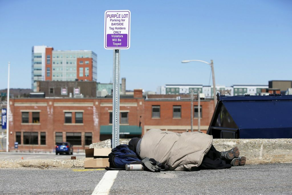In April, a man sleeps in a parking lot near the Oxford Street Shelter in Portland. A proposal calls for building a new city shelter away from the concentrated homeless services in Bayside.