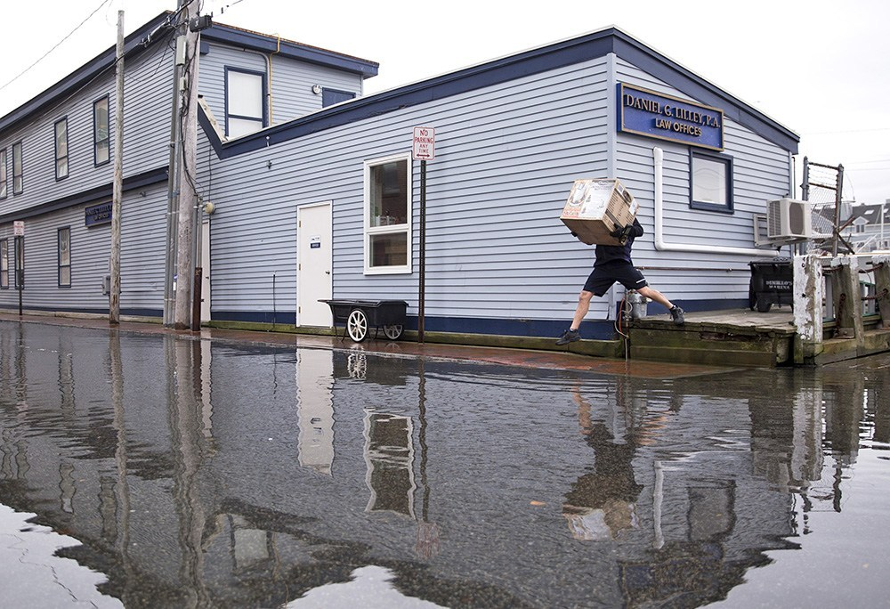 A FedEx delivery man jumps over pooling water on Portland Pier during a 2016 king tide.