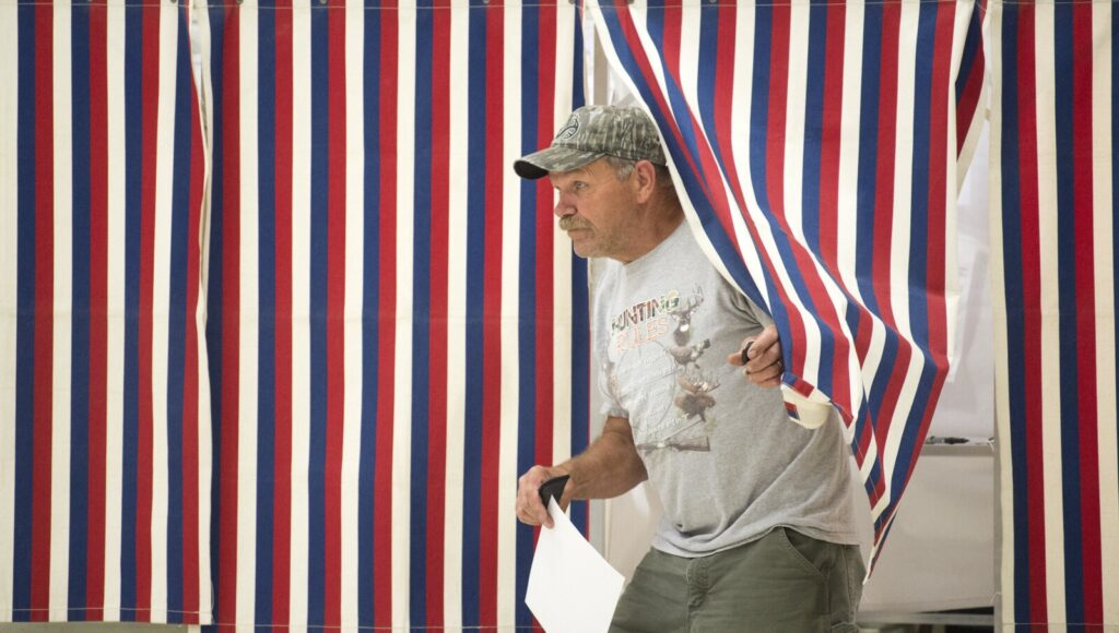 Jim Greene emerges from the voting booth Tuesday to cast his ballot on a new School Administrative District 49 budget at the Fairfield Town Office.