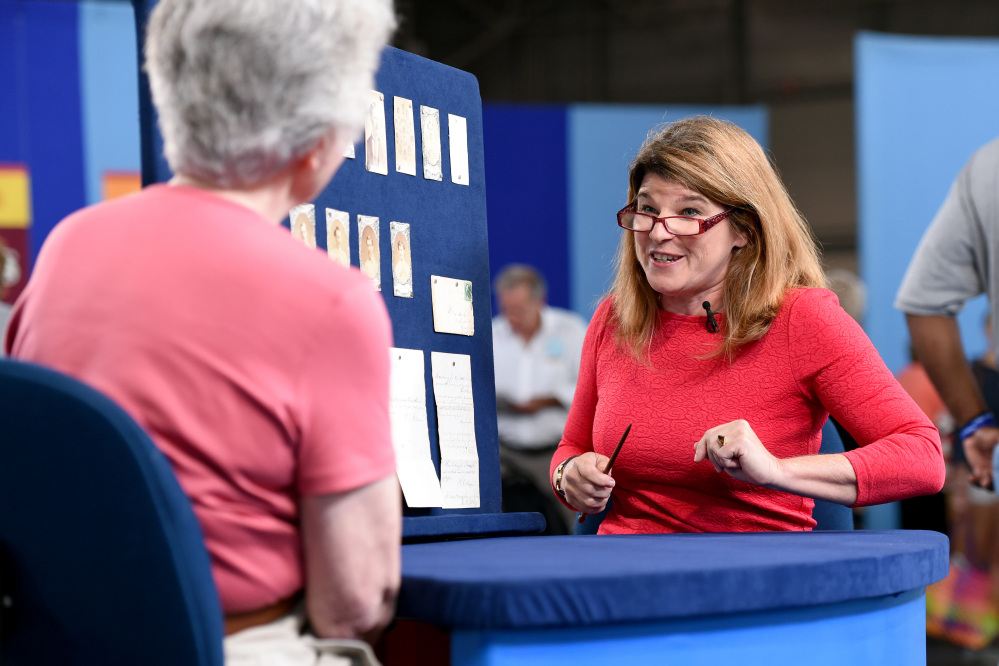 """This Aug. 9, 2014 photo released by """"Antiques Roadshow"""" shows Leila Dunbar appraising a collection of early Boston baseball memorabilia for the program in New York."""