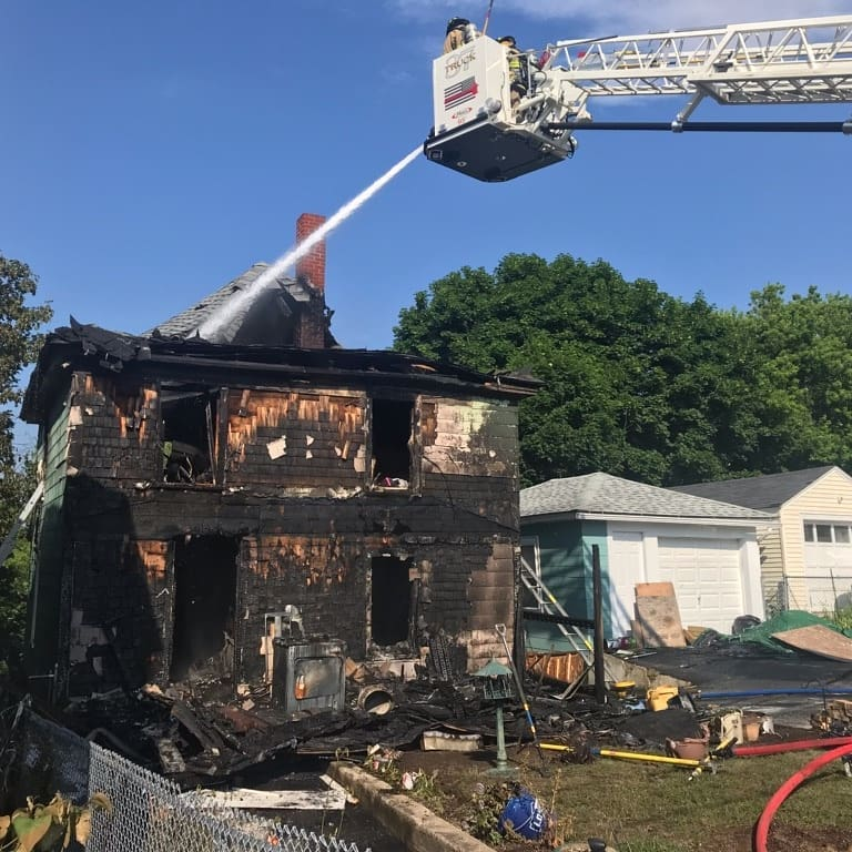 A Sanford ladder truck hoses down hot spots on Saturday at 26 Montreal St. The single-family home was destroyed by the arson fire.