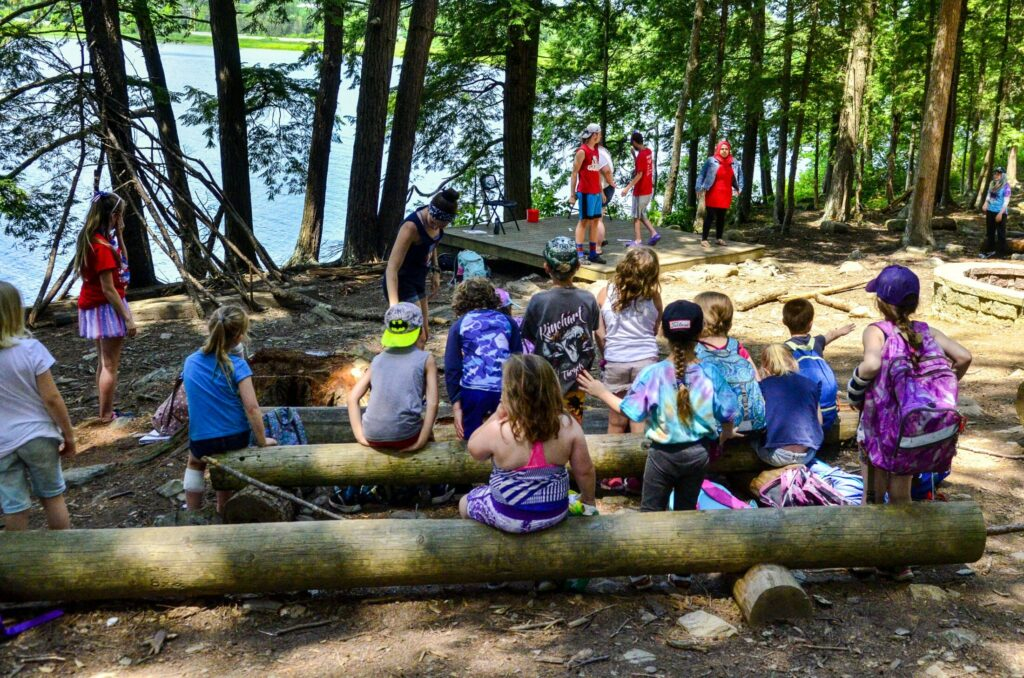 Campers assemble to watch a comedy quiz show Wednesday during a Kennebec Valley YMCA day camp at Camp KV in Readfield.