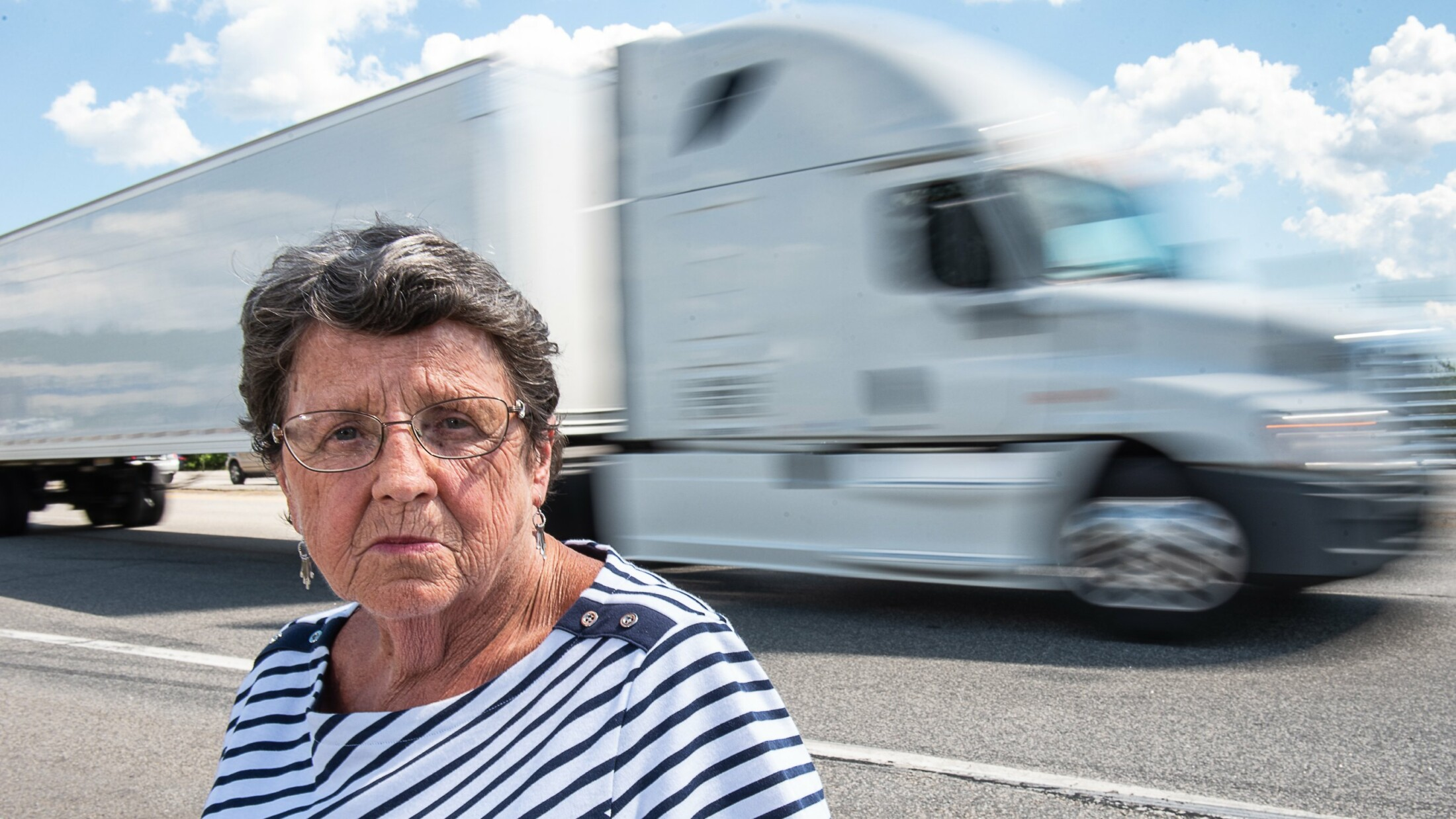 Daphne Izer watches tractor-trailers fly past on their way to the Maine Turnpike at the Auburn interchange Tuesday. Izer started Parents Against Tired Truckers in 1994, after her son and three of his friends were killed when a truck driver fell asleep and hit their car in the breakdown lane on the Maine Turnpike.