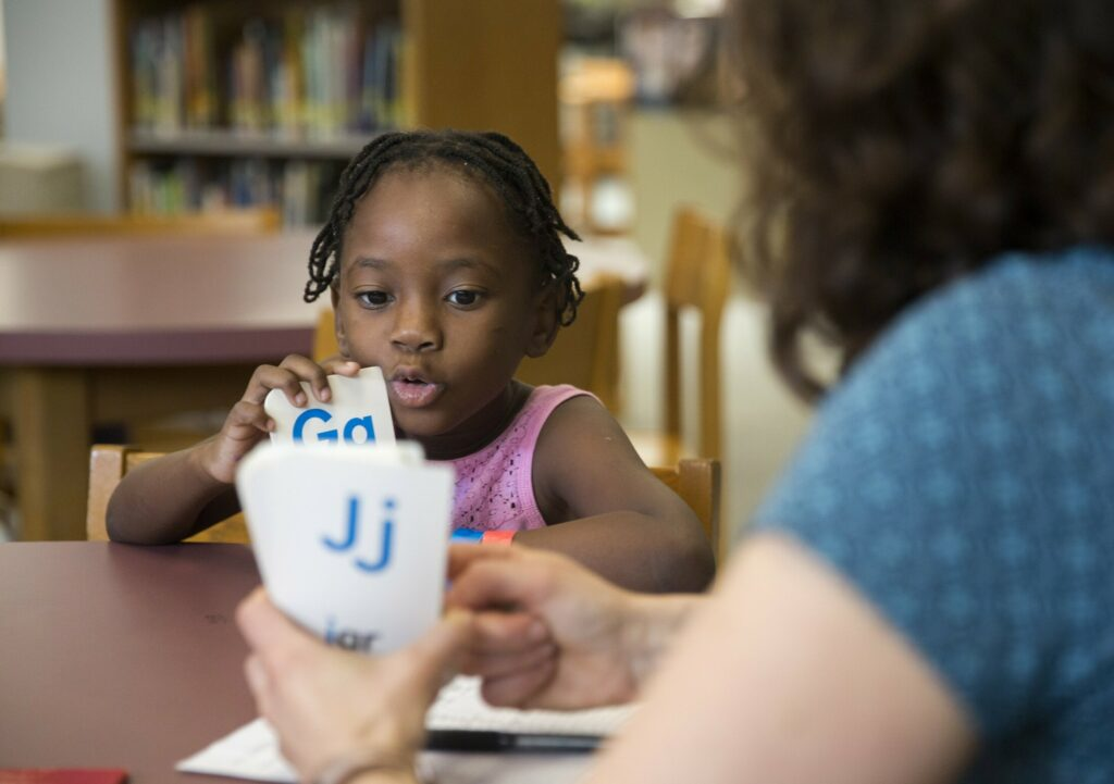 Emily Hall Greeley does an English language assessment with Stela Solani Ndombasi Mvemba, 5, at King Middle School on Wednesday. Stela is one of roughly 75 children of asylum seekers who are being processed and assessed by Portland Public Schools. Many of the children will start summer school next week.
