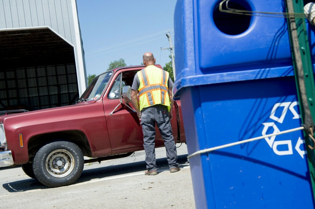 A worker at the Clinton-Benton Solid Waste and Recycling Transfer who did not want to be identified helps a resident with his refuse on Wednesday.