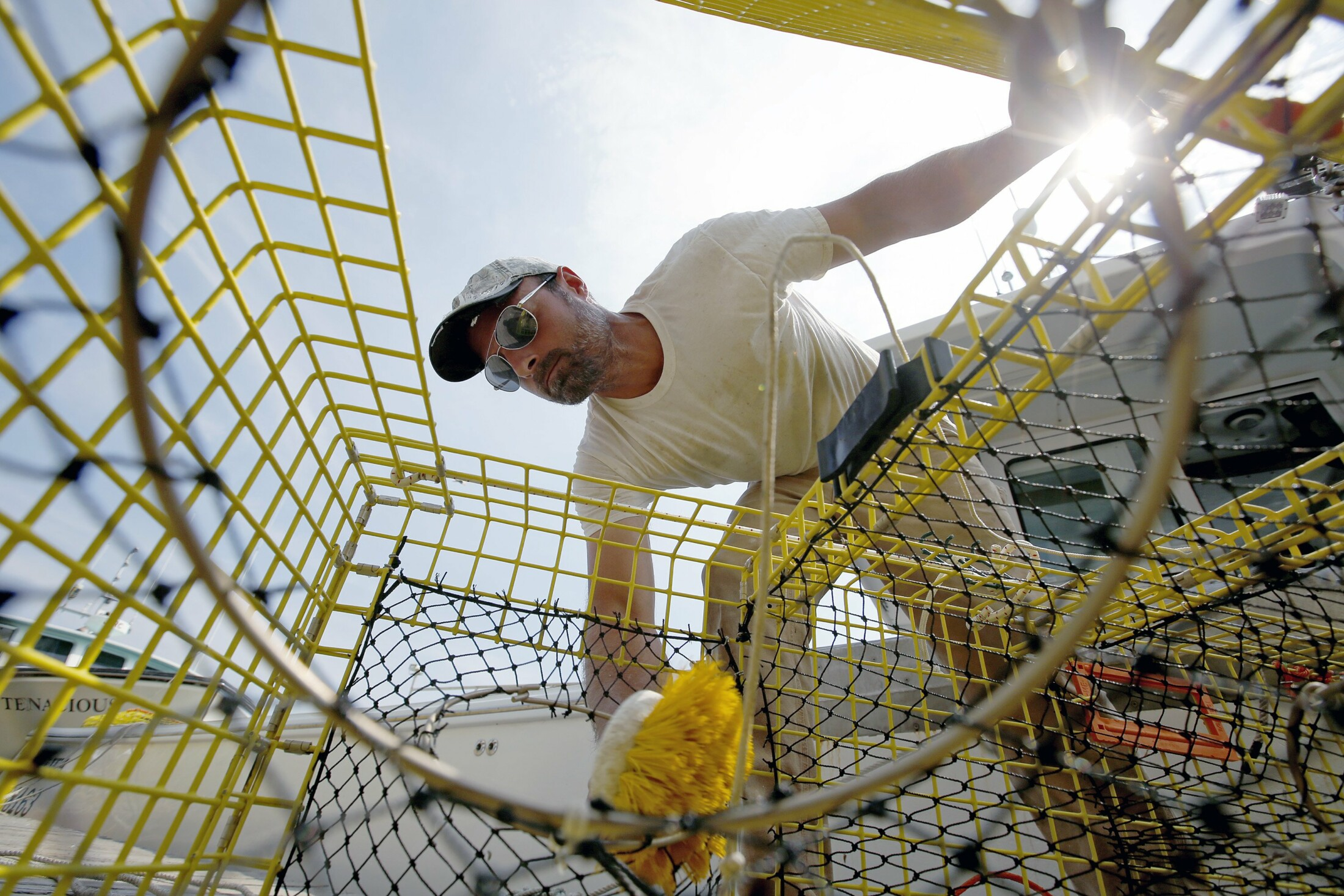 Joe Dyer, a sternman on the Jacalwa, cleans traps on Custom House Wharf in Portland. The Maine Department of Marine Resources has issued a plan intended to protect endangered right whales and the state's lobster industry that reduces vertical lobster lines. But the reductions are for lobstermen who fish beyond the 3-mile mark, which is a minority of the state's 5,000 licensed lobstermen.