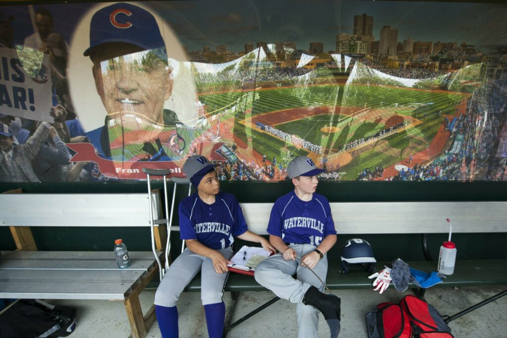 Waterville teammates Camden Brown, left, and Cormac Wilcox sit under a mural of Fran Purnell, whose name graces the Wrigley Field replica, during an 11U Cal Ripken state tournament game against Gardiner earlier this month. Waterville will host the 11U New England regional, which begins this weekend.
