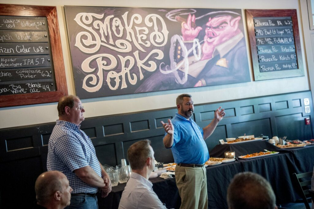 Derek Albert, senior project manager for Landry/French Construction, speaks with local business owners Tuesday about the upcoming construction of the new Colby hotel during an informational meeting at the Proper Pig in downtown Waterville.
