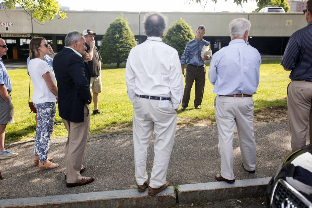 Attorney Jonathan Flagg, center, begins the bidding in a foreclosure auction for a strip of land in Portland in front of the Chestnut Street Garage. Massachusetts-based developed Ted Moore bought both the Portland land and property on Saco Island on Tuesday.