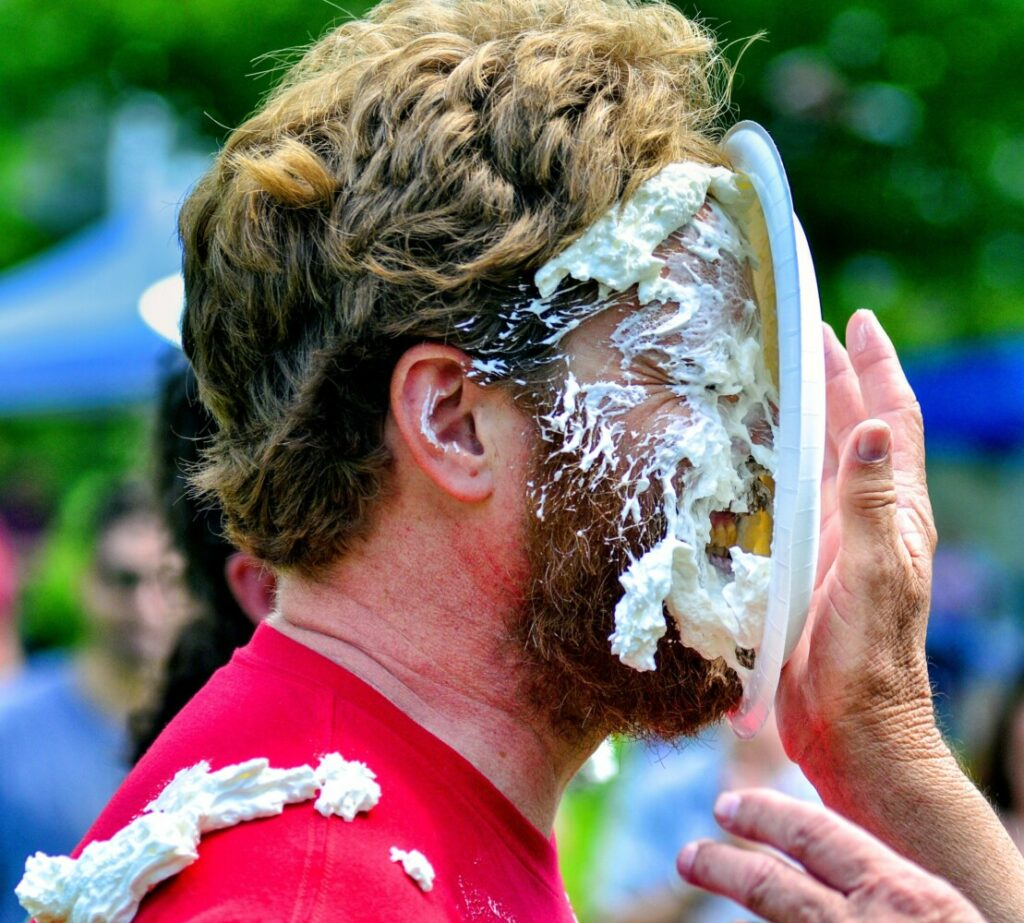 "Chase Morrill, of the ""Maine Cabin Masters"" television show, gets hit in the face with a plate of whipped cream Saturday during the Strawberry Festival in Wayne. There was a raffle for a chance to hit a cast member with a pie."