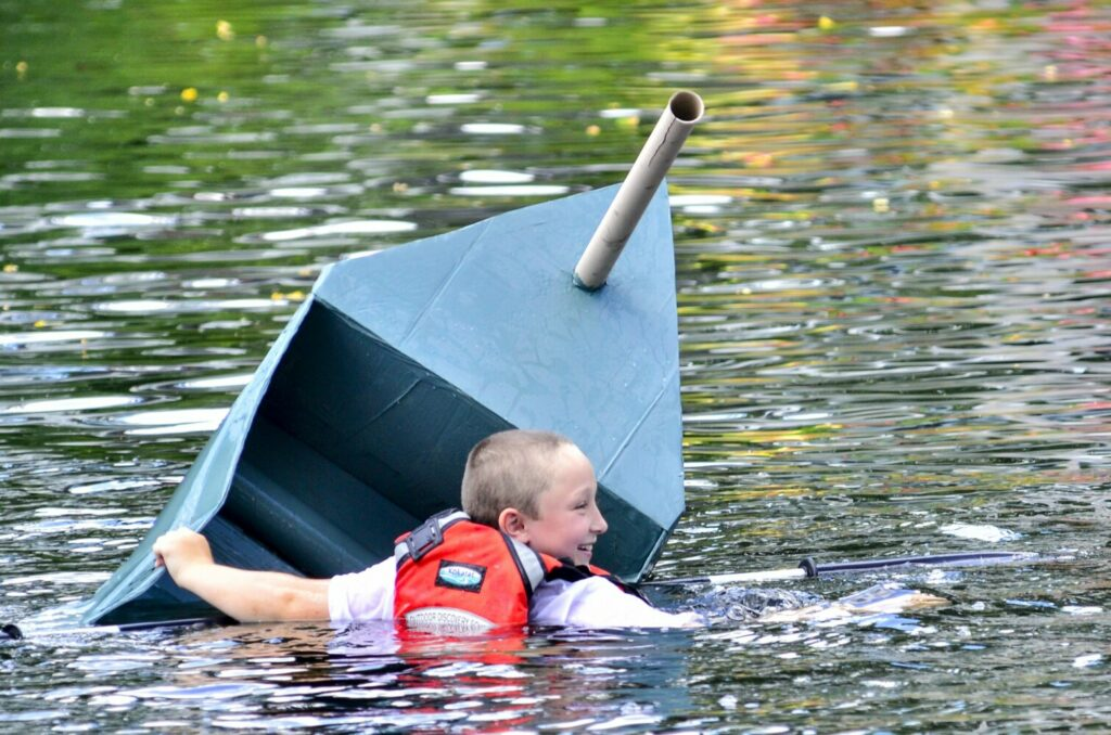 Isaac Stevenson swims in Mill Pond after his cardboard boat, S.S. Tuna, sank Saturday during a race at the Strawberry Festival in Wayne.