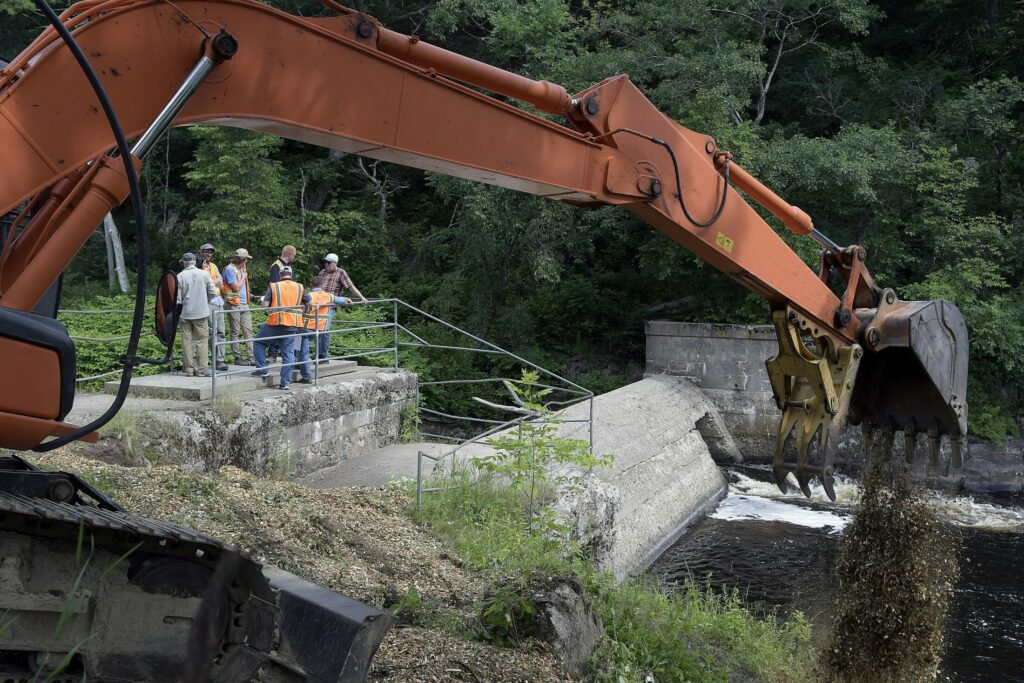 An excavator spreads wood chips Tuesday at the base of the Head Tide Dam in Alna, as construction begins on a modification of the dam's passages on the Sheepscot River.