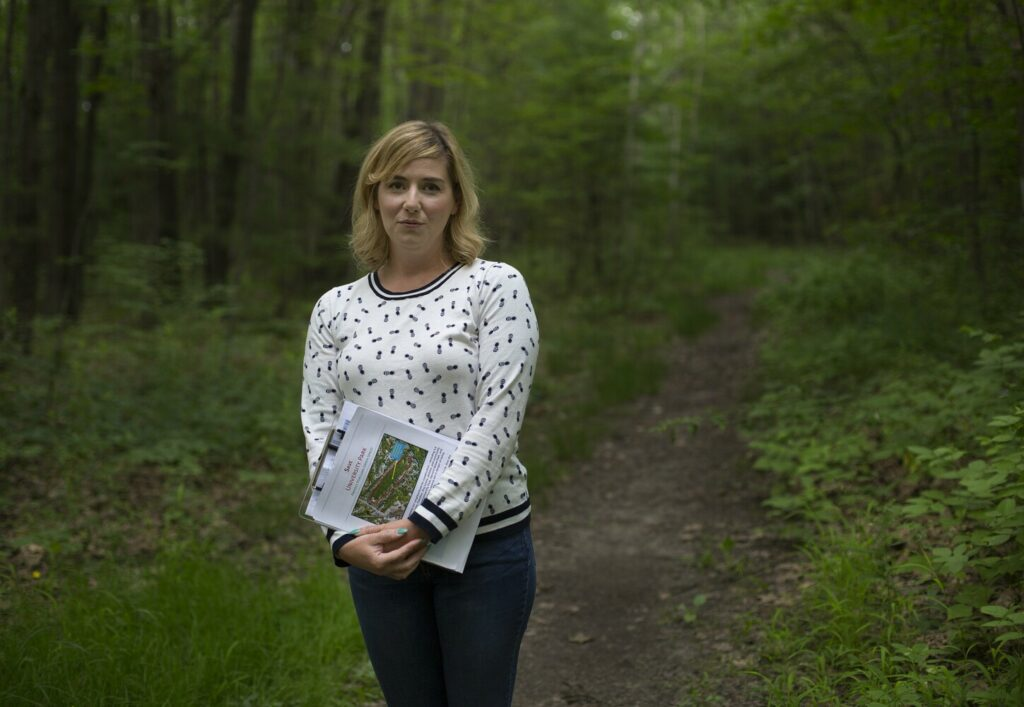 Elizabeth Rose helped organize opposition to a developer's proposal to rezone forestland near Morrill's Corner to allow construction of 20 duplexes. She is pictured in July on Harvard Path, which would become a paved street behind her house.