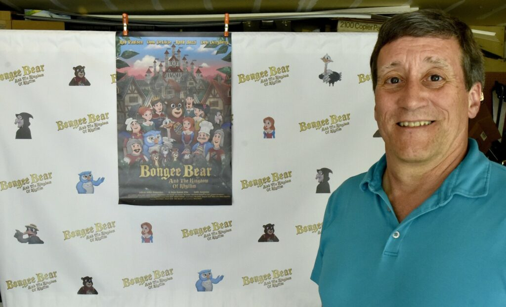 "Filmmaker Brian Zemrak, of Winslow, poses on Thursday before a wall hanging and poster of his animated movie, ""Bongee Bear and the Kingdom of Rhythm."" The movie will premiere Saturday during the Maine International Film Festival."