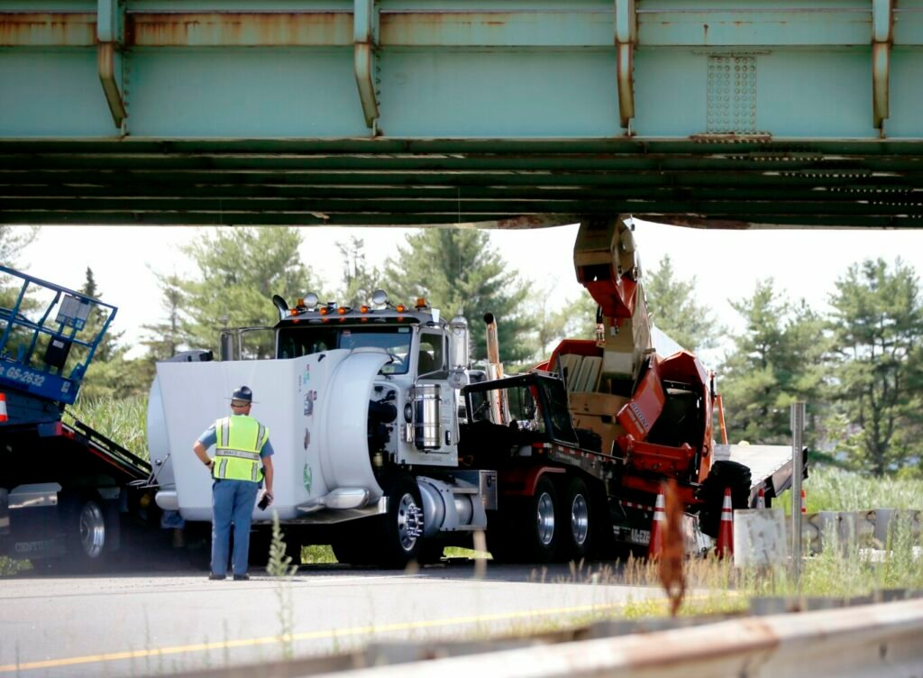 A truck hauling a small crane struck an overpass on the Maine Turnpike in the northbound lane near Exit 45 in South Portland on Monday.