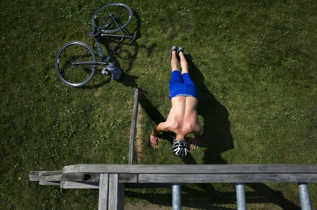 Mateo Hodo of Portland does exercises after riding his bike to Back Cove on Monday. He said that the heat doesn't bother him, and that he would be out doing the same thing if the temperature was in the nineties.