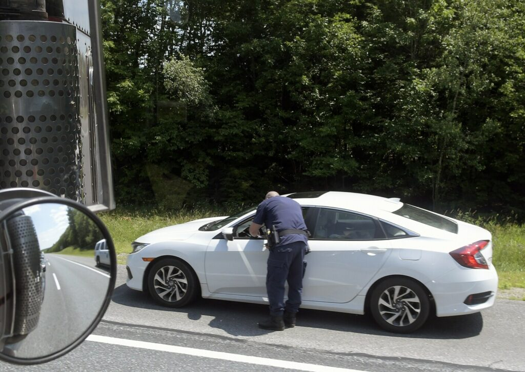 A Maine State Police trooper confers with a driver after pulling the vehicle over Monday on Interstate 95 in West Gardiner because of distracted driving. The department's Commercial Vehicle Unit was scrutinizing the operation of drivers across Maine for distracted driving last week as part of a nationwide effort. Troopers traveling in a tractor-trailer truck between Topsham and West Gardiner directed colleagues to drivers using cellphones or not wearing seat belts.