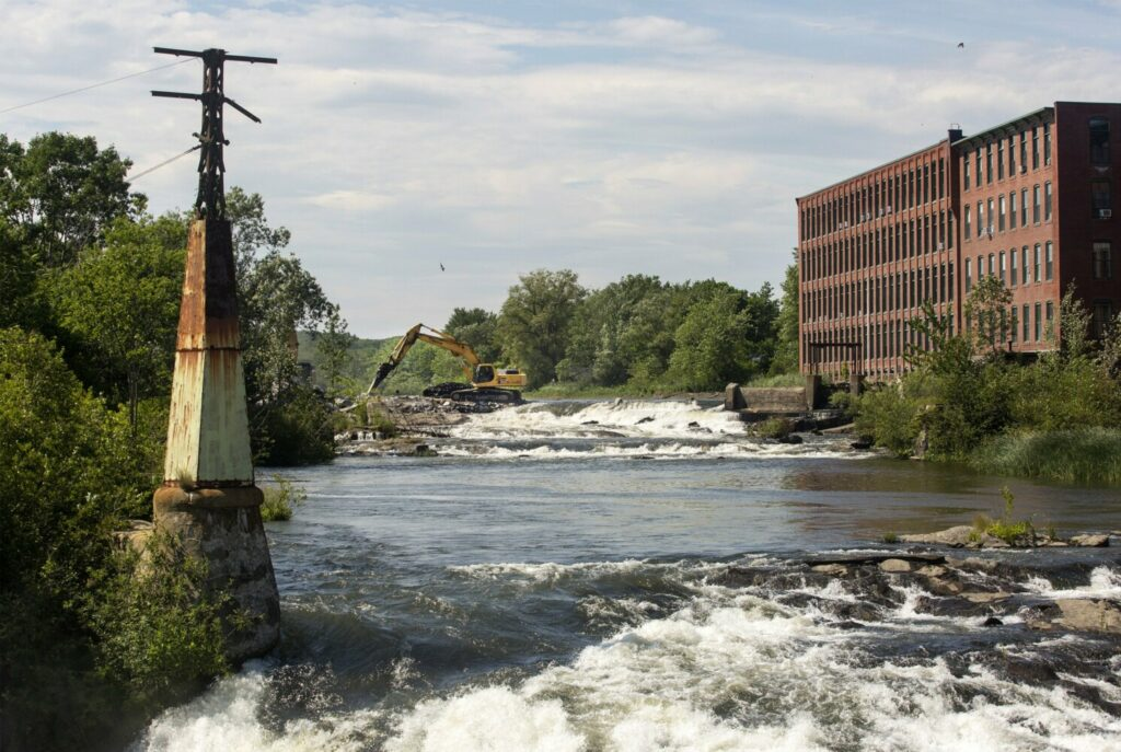 A crew begins work Tuesday to remove the Saccarappa Falls dam near Bridge Street in Westbrook. The dam's removal is a part of a settlement between the Sappi paper company and conservation groups.