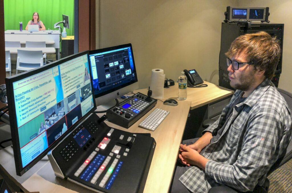 AUGUSTA, ME - JULY 17: Wendy St. Pierre, left, teaches Community Mental Health class as media services technician Luke Martin runs the board in control room on Wednesday July 17, 2019 at the University of Maine at Augusta. (Staff photo by Joe Phelan/Staff Photographer)