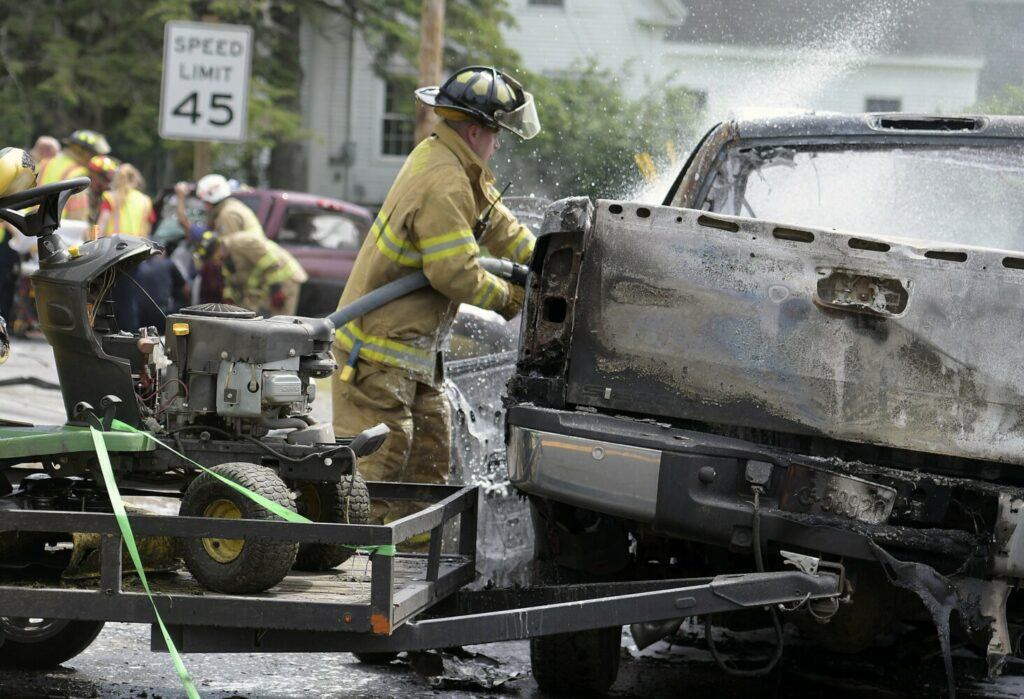 A firefighter extinguishes a burning pickup truck as colleagues extricate the driver of another pickup after the vehicles collided Wednesday on U.S. Route 201 in Richmond. Witnesses and neighbors removed the driver of the burning pickup moments before it exploded in flames.