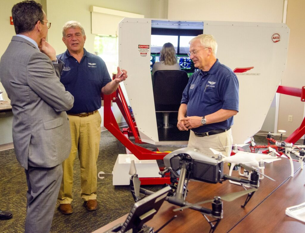 New University of Maine System Chancellor Dannel Malloy, left, chats with instructors Tom Abbott and Daniel Leclair about the flight simulator and drones used in the aviation program during a tour Tuesday at the University of Maine at Augusta.