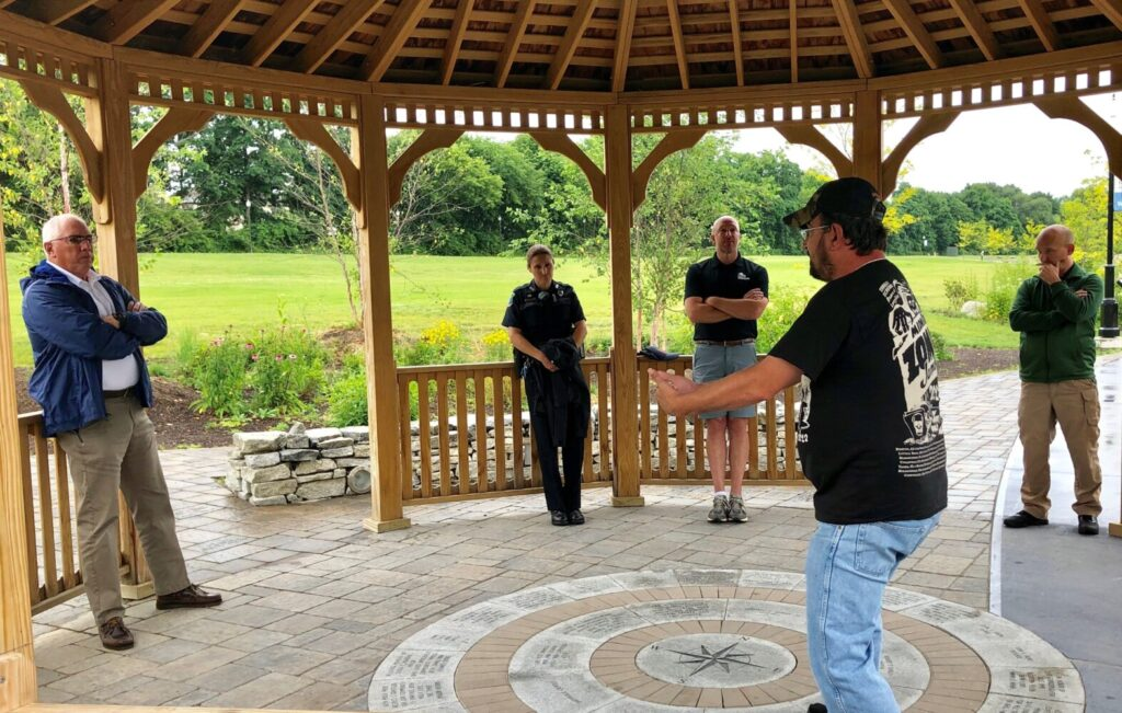A man who would only identify himself as Greg, front center, speaks with Waterville police Chief Joseph Massey, left, and other city officials during a gathering Tuesday morning in the gazebo at RiverWalk at Head of Falls in Waterville.