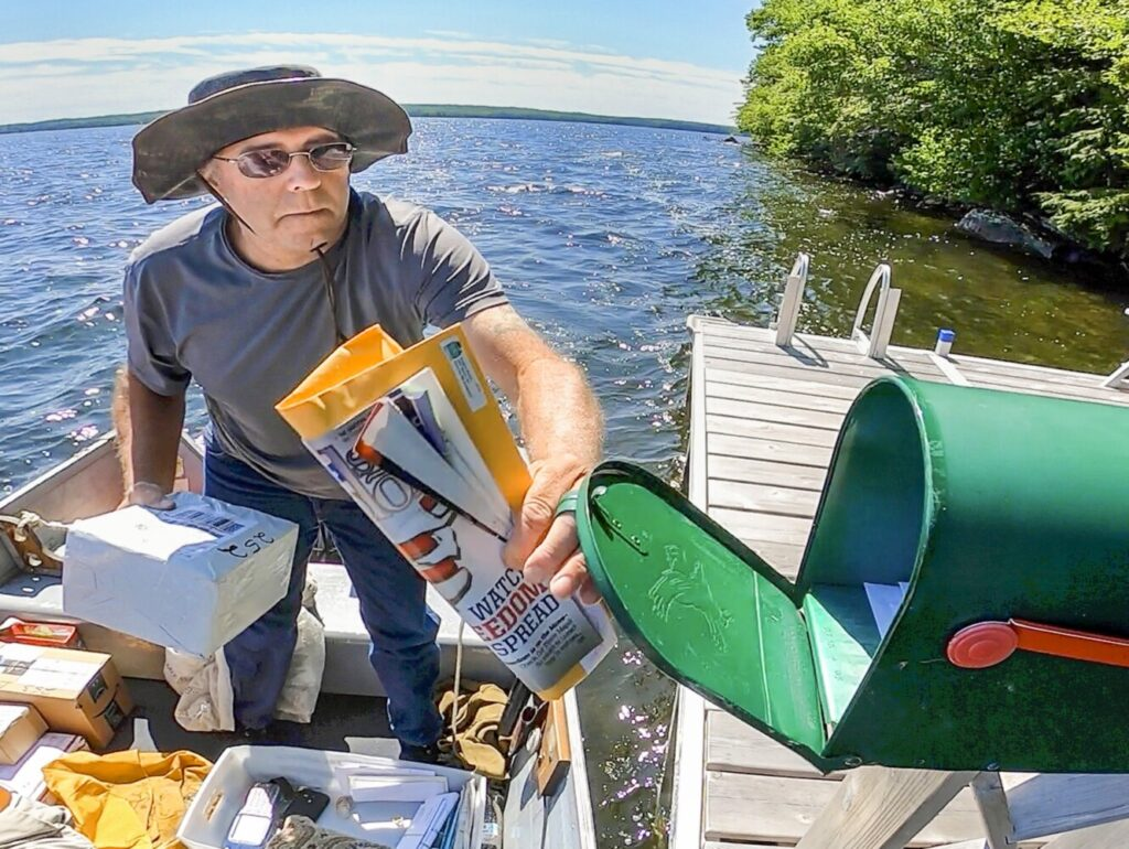 John Govostes Jr. opens a mailbox July 25 to put in a package on his watery route on Great Pond in Belgrade.