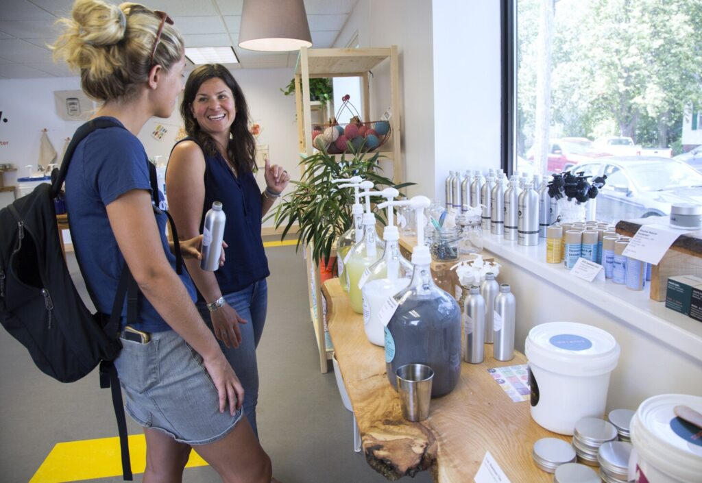 Laura Marston, center, owner of GoGo Refill, a store where customers can bring refillable containers to buy such products as laundry detergent, talks with Lexi Doudera, a customer who lives in the South Portland neighborhood.