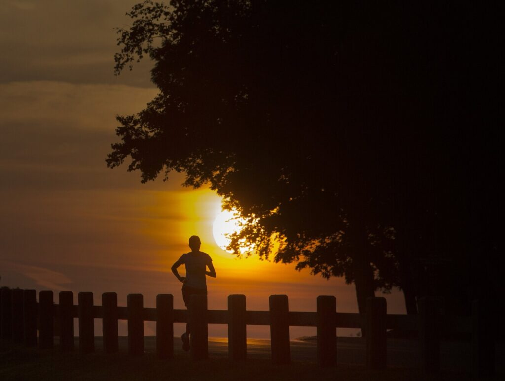 The sun rises behind a runner at Fort Williams Park in Cape Elizabeth on Tuesday. July was consistently warm this year, with a vast majority of the days a few degrees above average.